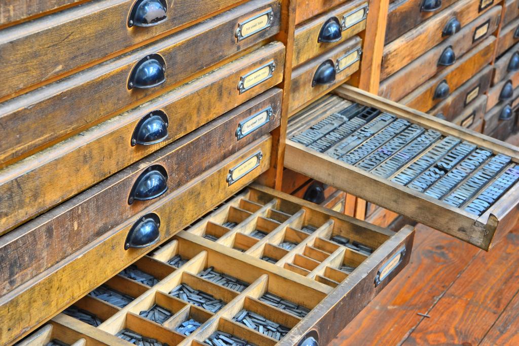 En la imagen vemos un chibalete, mueble donde se almacenan las cajas tipográficas y sus divisiones internas para los diferentes tipos que componen cada tipografía. Chibalete viene del francés chivalet, o caballete.